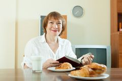 Mature  woman having breakfast with milk Royalty Free Stock Photo