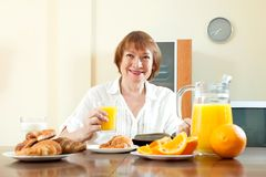 Mature  woman having breakfast with milk Royalty Free Stock Photography