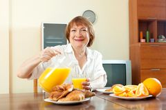 Mature  woman having breakfast Stock Photos