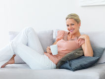 Mature woman having coffee while relaxing at home Royalty Free Stock Photography