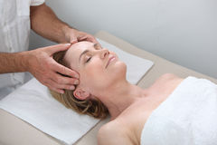 Mature woman having facial massage Stock Photos