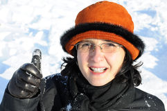 Mature woman having fun in snow giving thumb up Stock Images