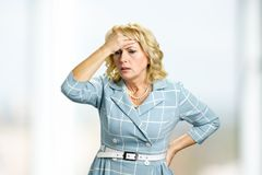 Mature woman having headache. Stressed busineswoman with headache, migraine or forgetfulness Royalty Free Stock Photo