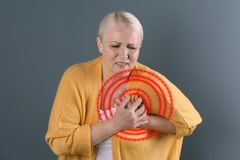 Mature woman having heart attack. On color background stock photo
