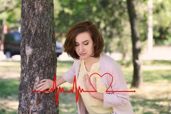 Mature woman having heart attack near tree. In park royalty free stock image