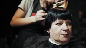 Hairstylist cut female hair during haircutting in hairdressing salon.