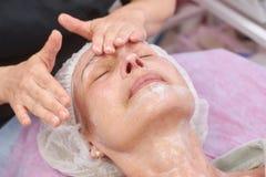 Mature woman having lymphatic massage. Mature women having lymphatic massage. Hands of cosmetian, facial cream. Instant face lift Stock Image