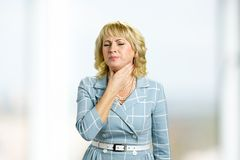 Mature woman having sore throat. Royalty Free Stock Image