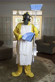 Mature woman in Haz Mat suit with blue broom and dust pan Stock Photography
