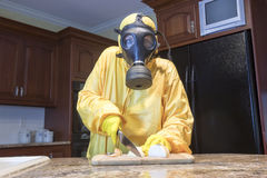 Mature woman in Haz Mat suit chopping onions Royalty Free Stock Photos