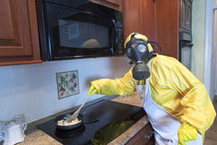 Mature woman in Haz Mat suit cooking Royalty Free Stock Images