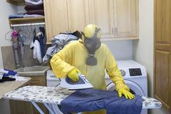Mature woman in Haz Mat suit ironing shirt on board with steam Royalty Free Stock Photo