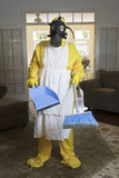 Mature woman in Haz Mat suit in living room with broom Royalty Free Stock Photo