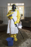 Mature woman in Haz Mat suit in living room with mop Royalty Free Stock Images