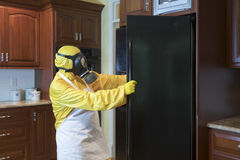 Mature woman in Haz Mat suit looking in refrigerator Royalty Free Stock Photography