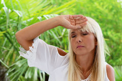 Mature woman with headache in summer heat Stock Image