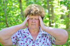 Mature woman with headache in the summer park Royalty Free Stock Photo
