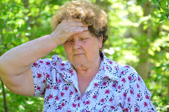 Mature woman with headache in the summer park Stock Photos