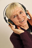 Mature woman with headphones. Portrait of happy mature woman wearing pair of headphones, studio background Stock Images