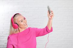 Mature woman in headphones with mobile device stock images