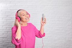 Mature woman in headphones with mobile device against brick wall royalty free stock photos