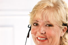 Mature woman headset smiling Royalty Free Stock Photography