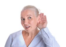Mature woman with hearing problem on white. Background stock photography