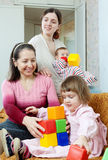 Mature woman and her adult daughter plays with children Stock Photo