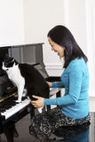 Mature woman and her cat jumping on keyboard of piano Stock Images