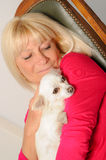 Mature Woman with her dog. At home Royalty Free Stock Photography