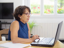 Mature woman with her laptop in the house Royalty Free Stock Photography
