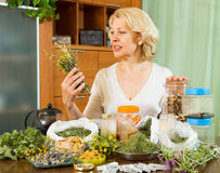Mature woman with herbs at table Stock Photos