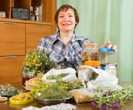 Mature woman with herbs at table Royalty Free Stock Image