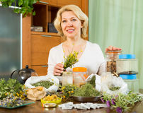 Mature woman with herbs at table Royalty Free Stock Photos