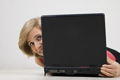 Mature woman hide behind laptop. Smiling mature woman hiding behind laptop  and lying down on wooden floor,see more in People on couch or wooden floor Stock Photography