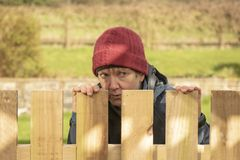 Mature woman hiding behind fence. Outdoors stock photography