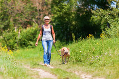 Mature woman hiking with dog in the landscape Stock Photo