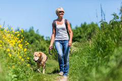 Mature woman hiking with a dog Royalty Free Stock Photos