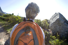 Mature woman hiking on mountain trail in bright sunlight, carrying orange rucksack, rear view royalty free stock images