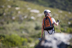Mature woman hiking on mountain trail, carrying rucksack and using hiking pole, rear view royalty free stock photography