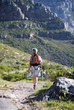 Mature woman hiking on mountain trail, carrying rucksack, using hiking pole, rear view royalty free stock photo