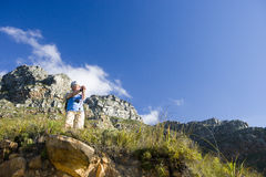 Mature woman hiking on mountain trail, leaning on hiking pole, admiring scenery, smiling, low angle view Royalty Free Stock Photography