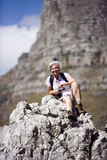 Mature woman hiking on mountain trail, sitting on rock, taking break, smiling, portrait stock photo