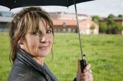 Mature woman hold umbrella Stock Photos