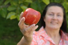 Mature woman holding an apple. Mature woman showing off an apple in her garden; senior healthy lifestyle concept Royalty Free Stock Photography