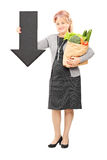 Mature woman holding a bag and big arrow pointing down Royalty Free Stock Image