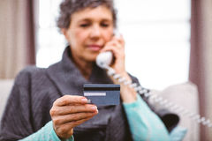 Mature woman holding credit card while talking on telephone Stock Images
