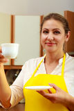 Mature woman holding cup of coffee in kitchen. Stock Images