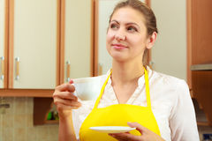 Mature woman holding cup of coffee in kitchen. Stock Photo