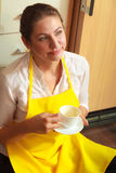 Mature woman holding cup of coffee in kitchen. Royalty Free Stock Photos